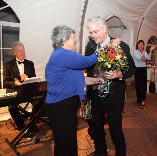 Retiring teacher and drama director Michael McGarty receives a hug and a bouquet of flowers from Schools Trust board member Weezie Potter, as well as a standing ovation from the crowd in recognition of his 34 years at Bromfield.